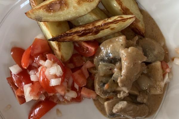 Gryterett av svinestrimler, champignon, paprika, løk og hvitløk, med tomat-og løksalat og slottspotet