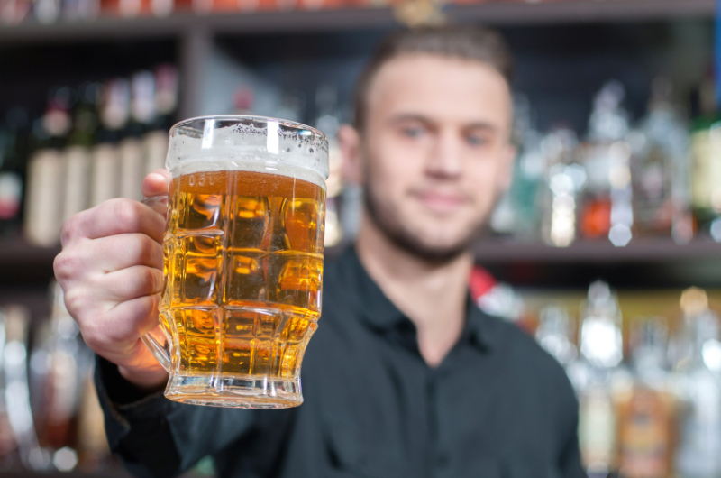 Young smiling bartender with beer on the bar