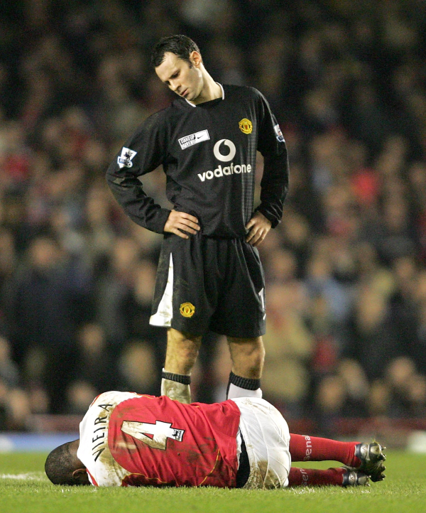 LONDON, ENGLAND - FEBRUARY 1: Patrick Vieira of Arsenal lies on the ground while Ryan Giggs of Manchester United down at him during the Barclays Premiership match between Arsenal and Manchester United at Highbury on February 1 2005 in London, England. (Photo by John Peters/Manchester United via Getty Images) *** Local Caption *** Patrick Vieira;Ryan Giggs