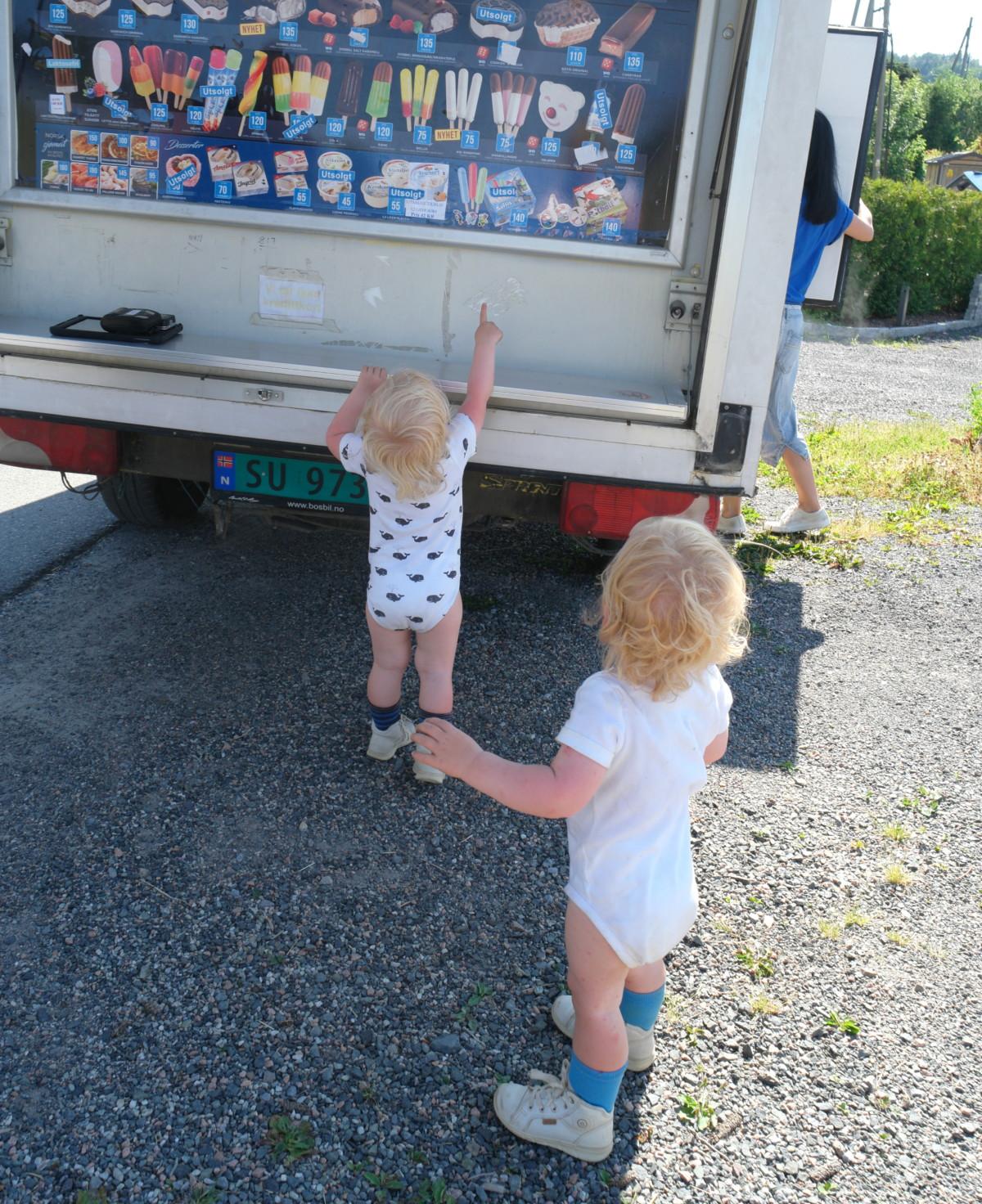 tvillinger på to år står bak isbilen og velger is