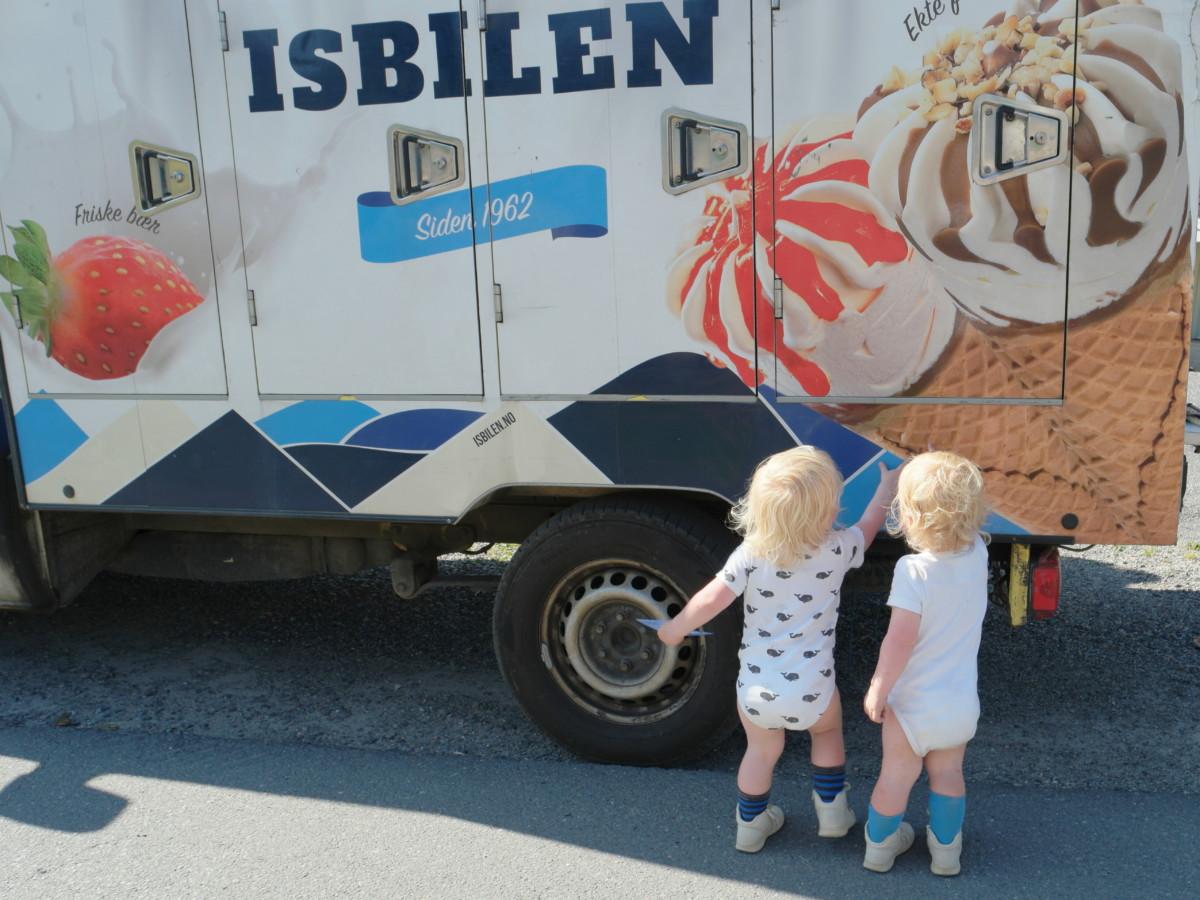tvillinger på to år peker på isbilen fra siden