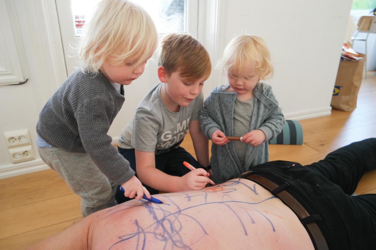 tre barn som tegner på en rygg med tusjer