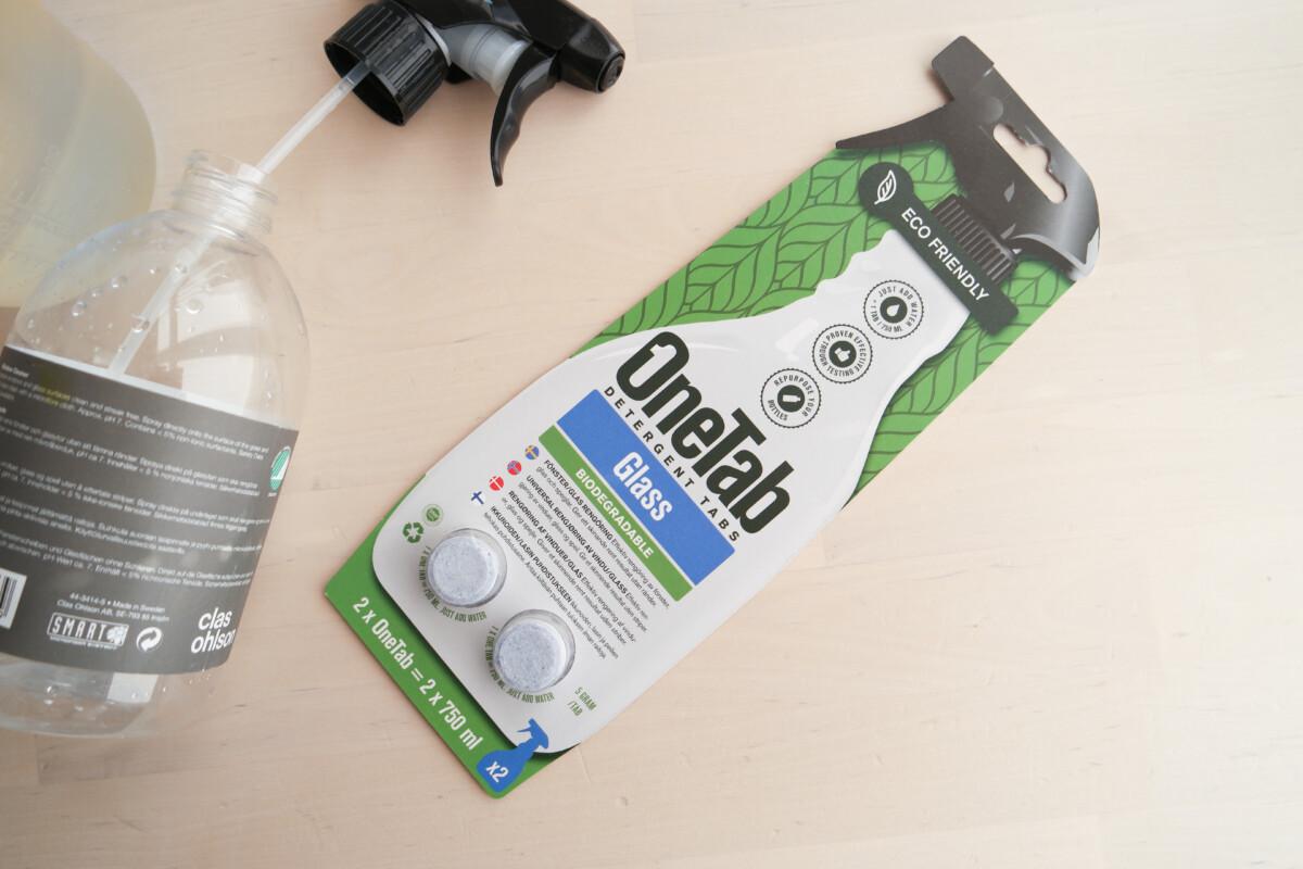 onetab rengjøringstablett pakke på bord med tom sprayflaske ved siden av