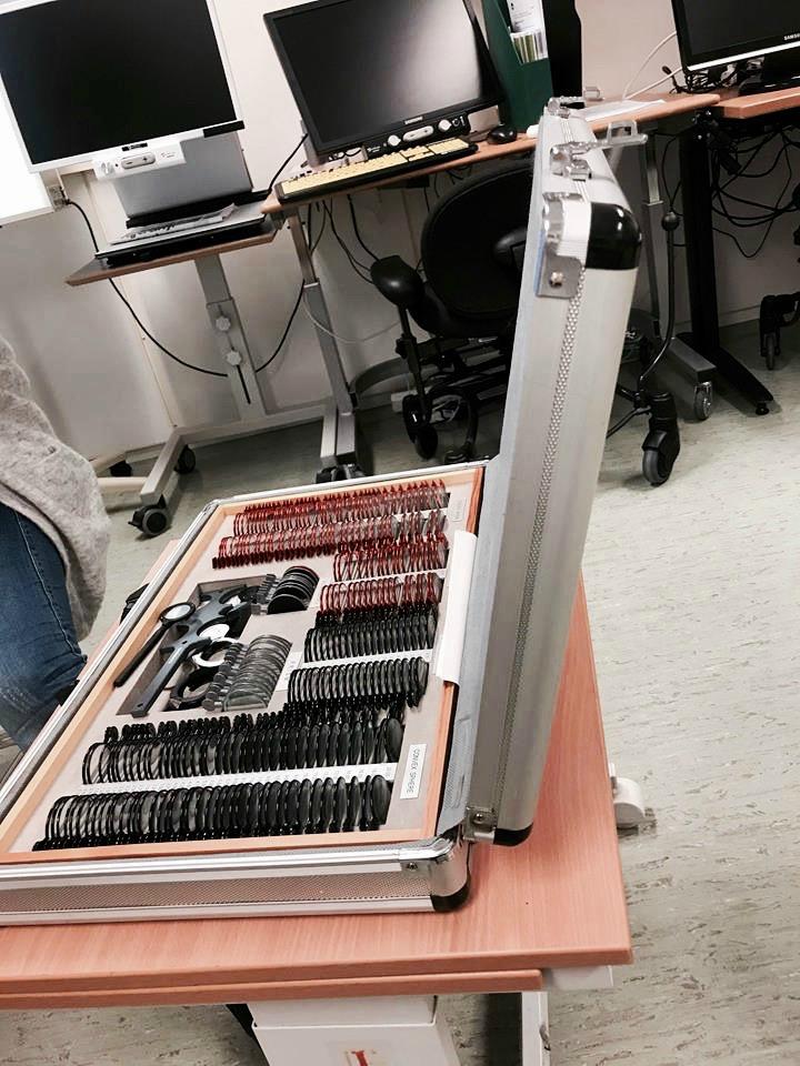 802b94b6297f Bildebeskrivelse  En stor koffert med brilleglass ligger oppå et bord. I  bakgrunnen er det to forskjellige typer lesetv