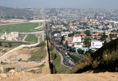 A small fence separates densely populated Tijuana, Mexico, right, from the United States in the Border Patrol?s San Diego Sector. Construction is underway to extend a secondary fence over the top of this hill and eventually to the Pacific Ocean.