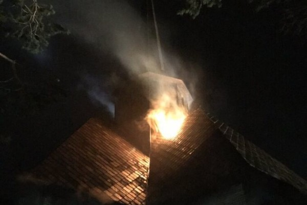 Det brenner natt til torsdag i Dombås kirke i Dovre kommune, og det var en stund åpne flammer utvendig