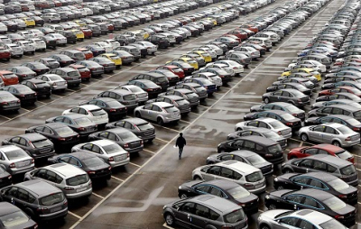 An employee walks past new cars at the parking lot of Changan Ford Mazda Automobile Co. Ltd, Ford Motor's joint venture in China, in Chongqing Municipality, October 12, 2010. Automakers in China shipped 19.3 percent more passenger cars to dealers in September from a year ago, official data showed, extending a rebound begun in August ahead of the peak auto sales season.