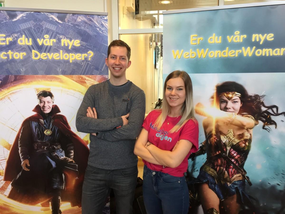 Elise og Jørgen som står foran to reklameplakater for aplia