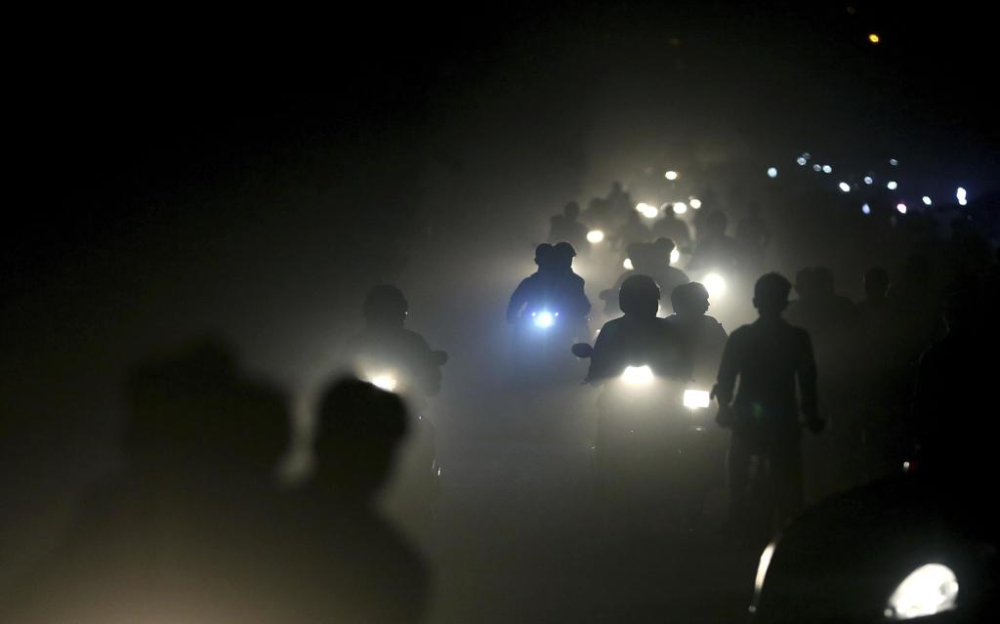 In this Friday, Nov. 10, 2017 file photo, Indian motorists ride past a thick blanket of smog and dust on the outskirts of New Delhi, India. The most recent air pollution data from the World Health Organization gives India a dubious lead. Ten Indian cities lead the list of the 20 most polluted cities in the world. (AP Photo/Altaf Qadri, File)