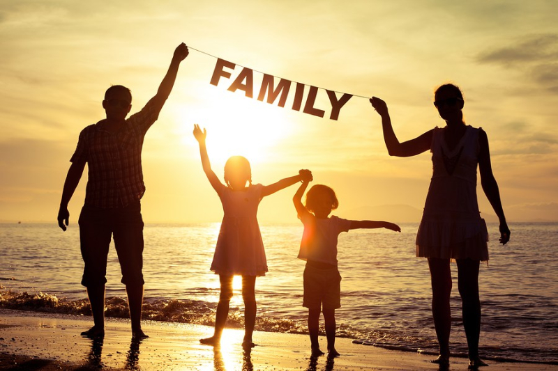 Happy family standing on the beach at the sunset time. Parents hold in the hands inscription