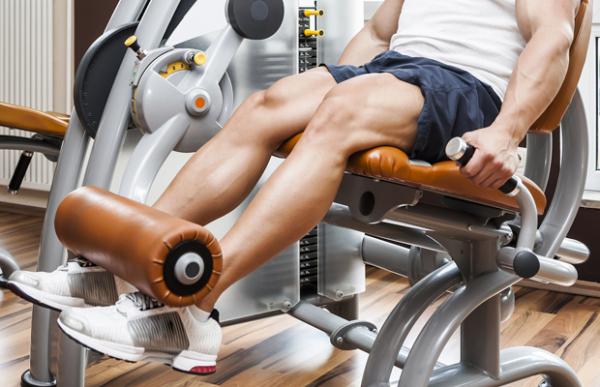 A handsome young muscular sports man doing leg press