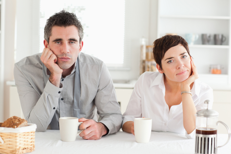 Tired couple drinking coffee in a kitchen