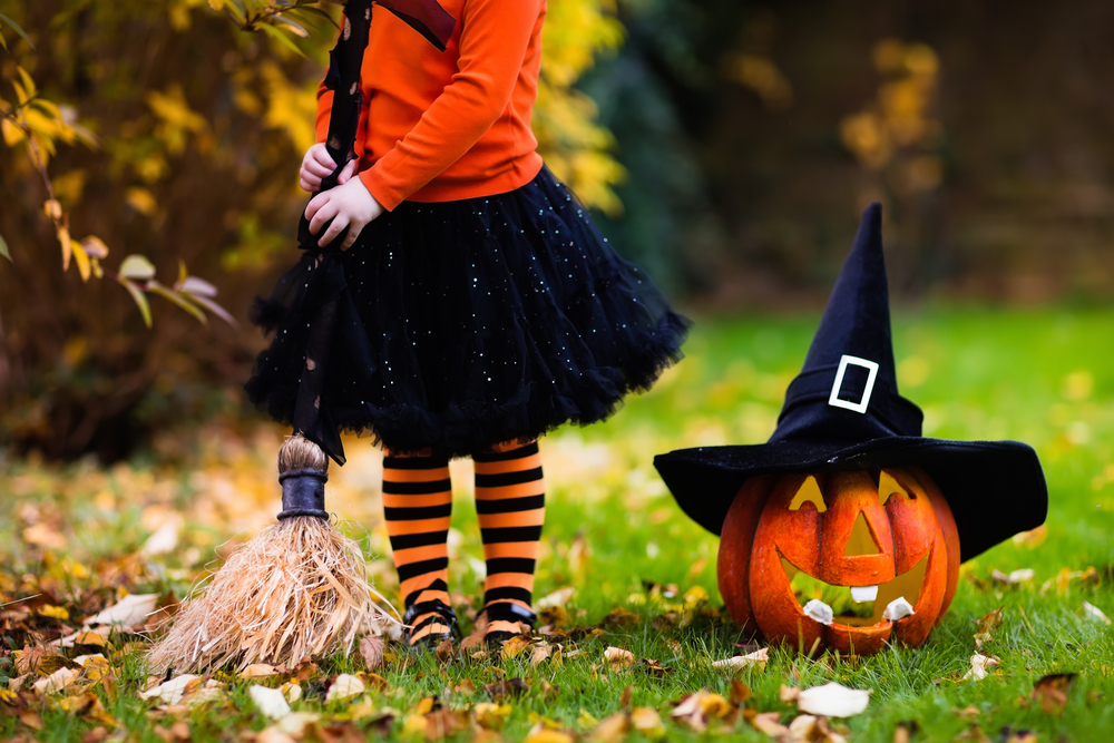 Little girl in witch costume playing in autumn park. Child having fun at Halloween trick or treat. Kids trick or treating. Toddler kid with jack-o-lantern. Children with candy bucket in fall forest.