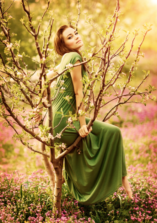 Fairy-tail forest nymph, beautiful sexy woman at spring garden, wearing long dress, sitting on blooming tree, vintage dreamy fashion style