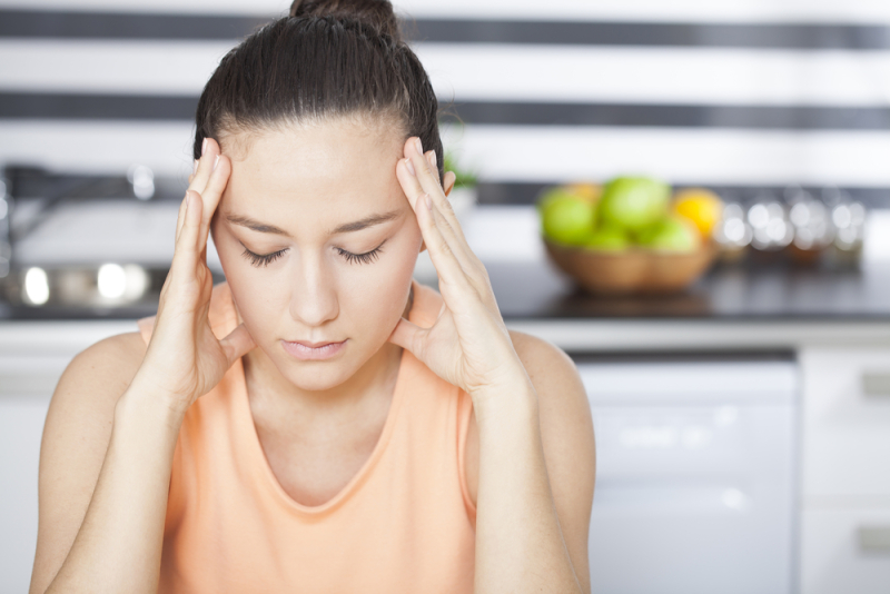 Stressed young woman in kitchen