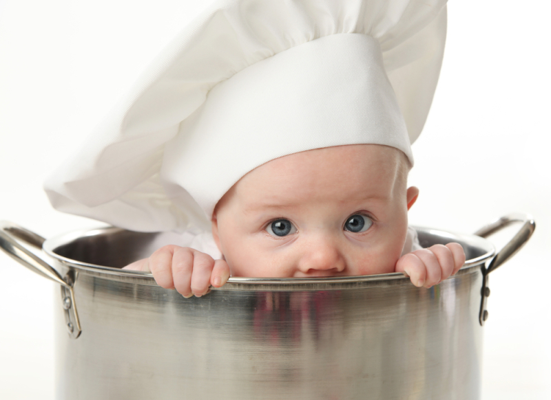 Close up portrait of a baby sitting wearing a chef hat sitting inside a large cooking stock pot, isolated on white