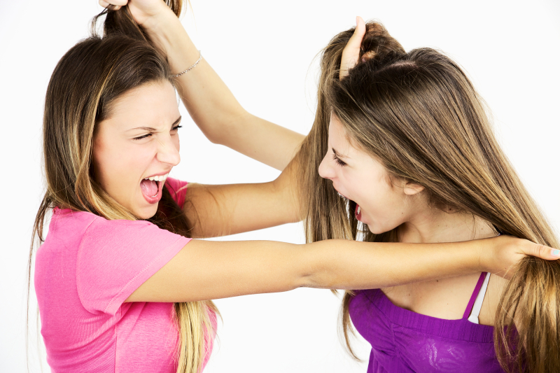 Angry girls fighting holding hair