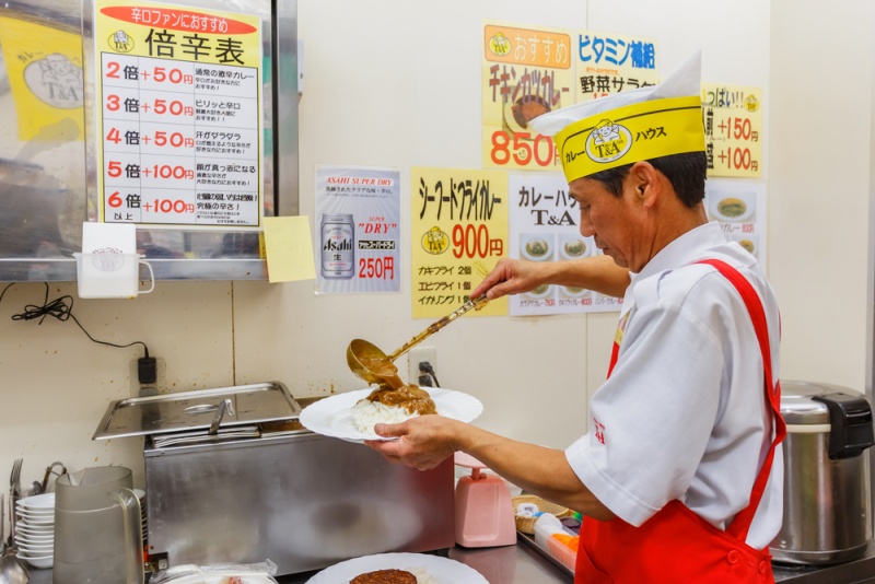 OSAKA, JAPAN - NOVEMBER 17: Japanese Curry Chef in Osaka, Japan on November 17, 2013. A Japanese curry chef prepares rice with curry at his restaurant in Dotonbori street
