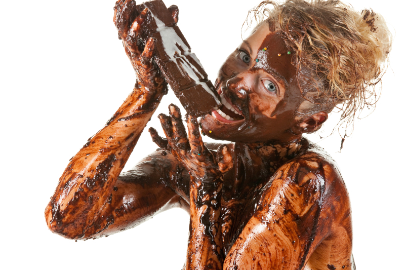 naked blond girl eating chocolate with melted chocolate all over her