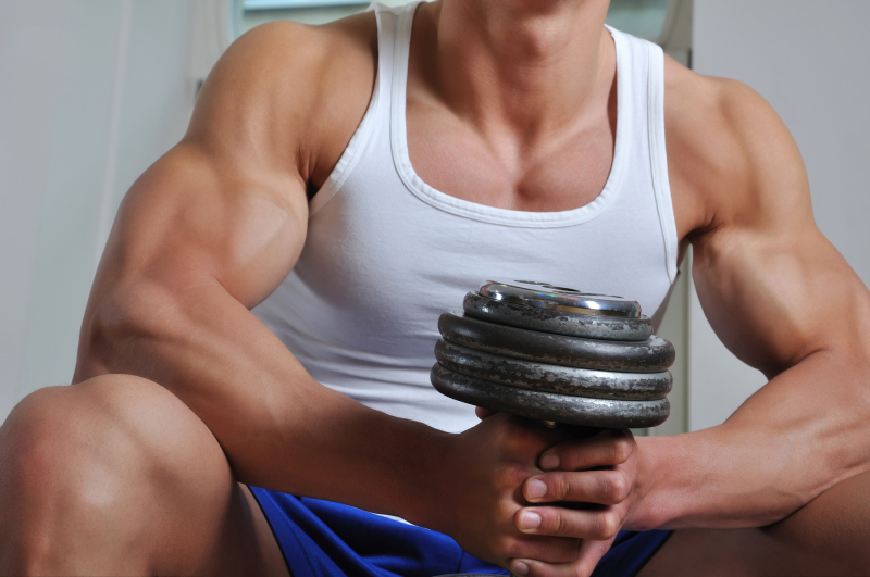 Powerful muscular man lifting weight