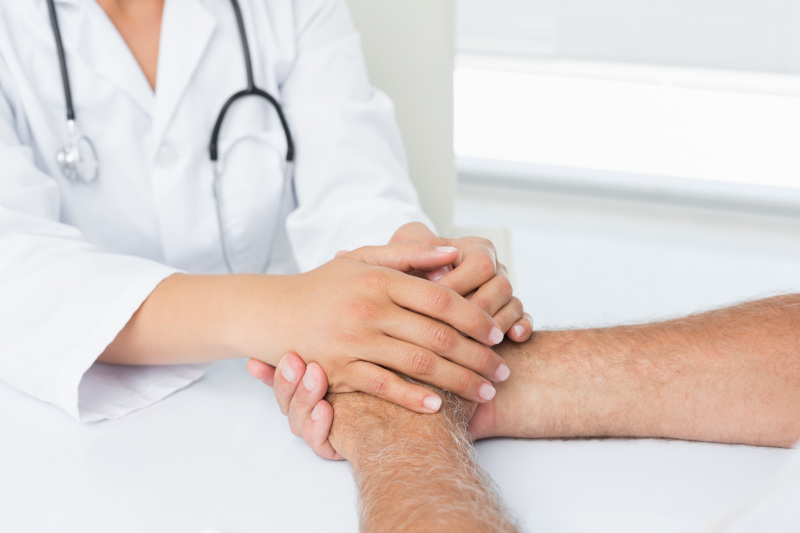 Close-up mid section of a doctor holding patients hands at medical office
