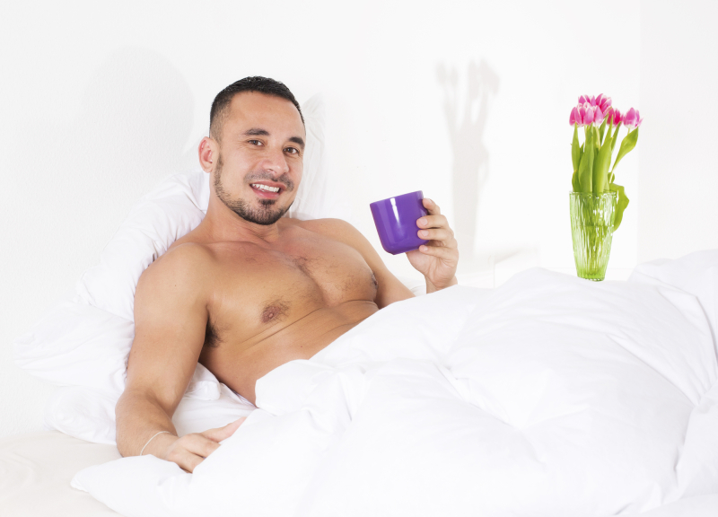 man in bed with naked torso holding a cup