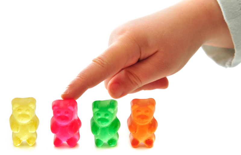 Foyr of colorfoul gummy bears on white background