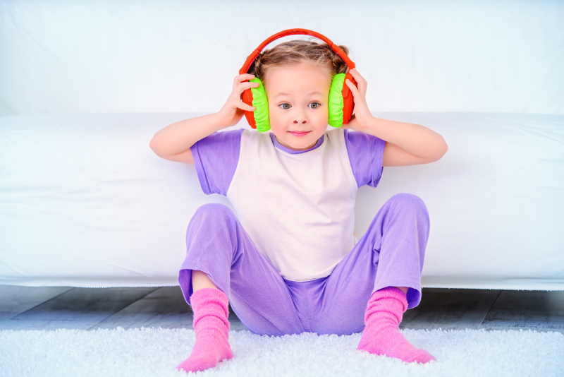 Cute little girl listens to music in headphones at home. Leisure. Family at home.
