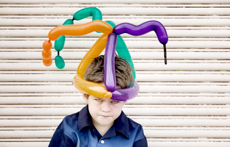 Young boy wearing a balloon hat with an angry face