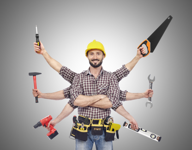Cheerful carpenter looking at camera with tolls in six hands, white background