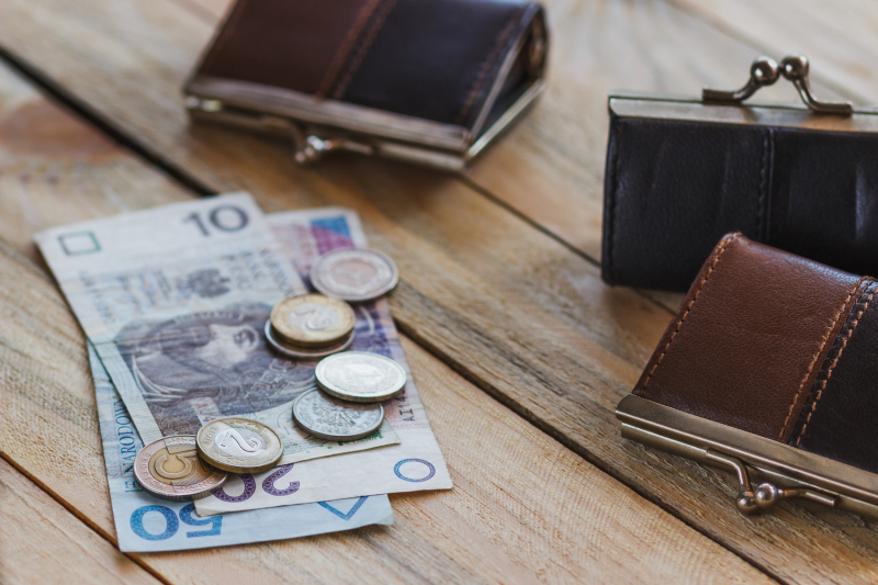 Polish zloty with little wallets on the old wooden background, soft focus background