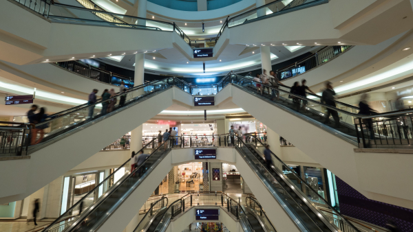 Big light multistorey shopping mall. Customers using escalators to get up and down. Trade centre of Petronas Twin Towers in Kuala Lumpur, Malaysia