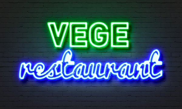 Vege restaurant neon sign on brick wall background